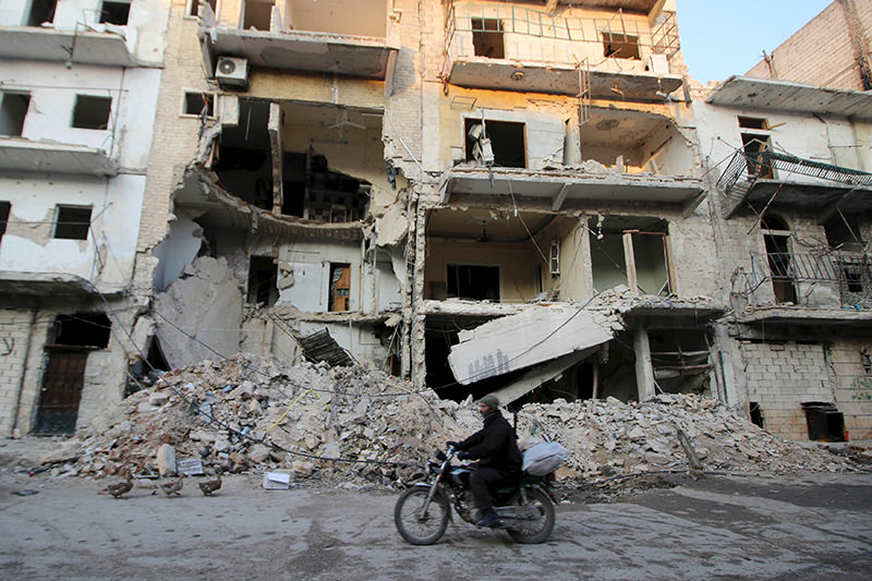 A man rides a motorcycle past damaged buildings in al-Myassar neighborhood of Aleppo, Syria January 31, 2016. (REUTERS Photo)