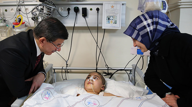 Prime Minister Ahmet Davutou011flu visiting a cancer patient with his wife Sare Davutou011flu at a children's hospital in Ankara (AA Photo)