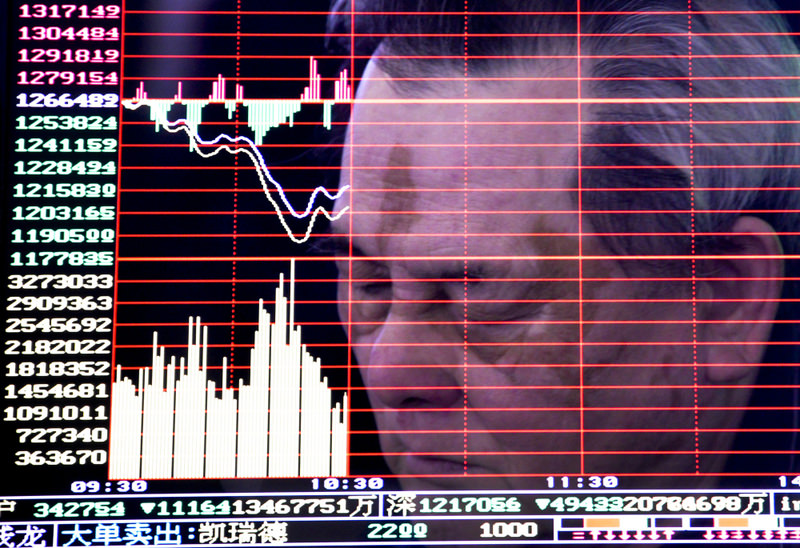 A man reflected on a screen displaying the stock index at a brokerage house in Handan in northern China's Hebei province.