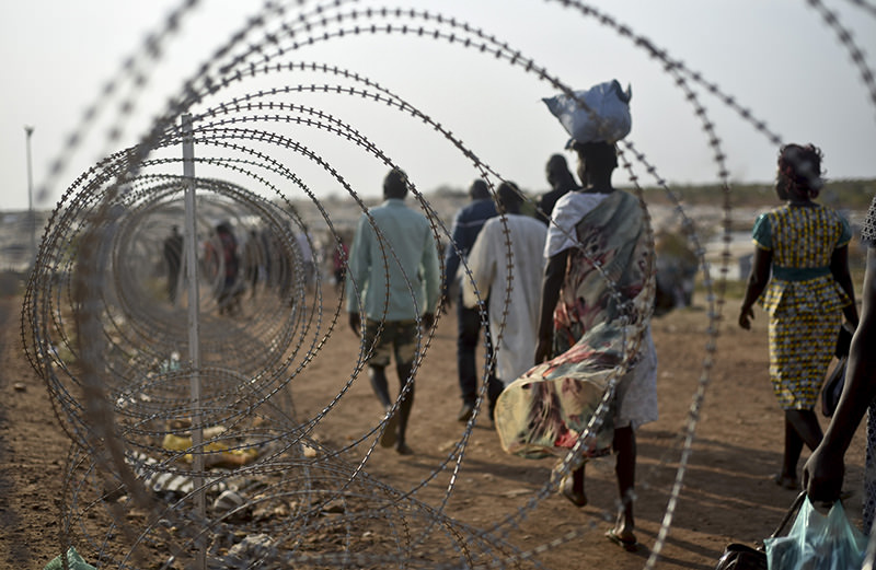 In this Jan. 19, 2016 photo, displaced people walk next to a razor wire fence at the United Nations base in the capital Juba, South Sudan (AP Photo)