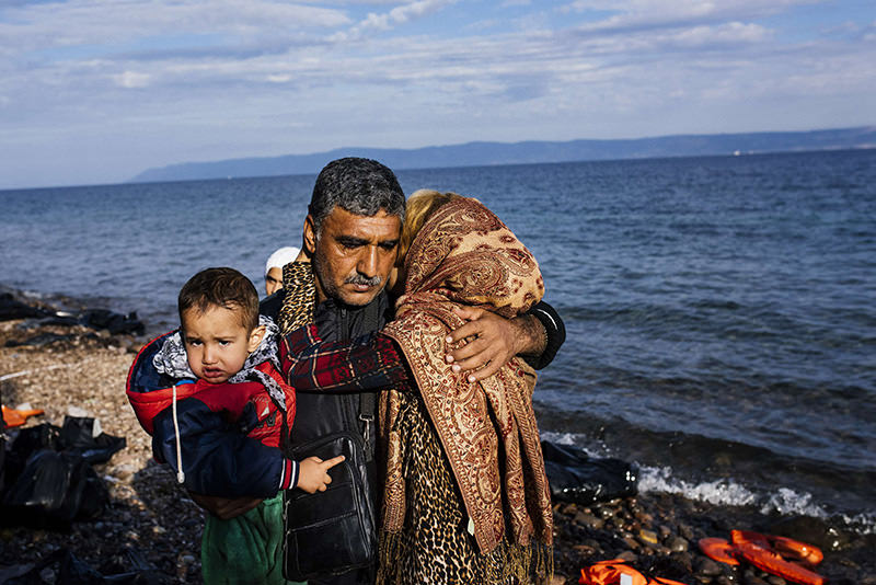 Representational photo: A family reacts shortly after arriving with other refugees on the Greek island of Lesbos on Oct 12, 2015 (AFP)