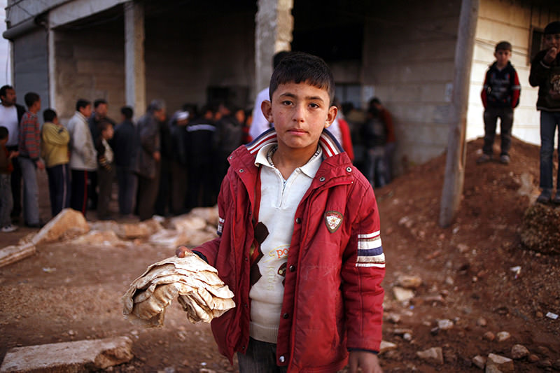 A Syrian boy holding bread distributed by Turkish NGO u0130HH in a refugee camp located in Turkeyu2019s southeastern province of u015eanlu0131urfa