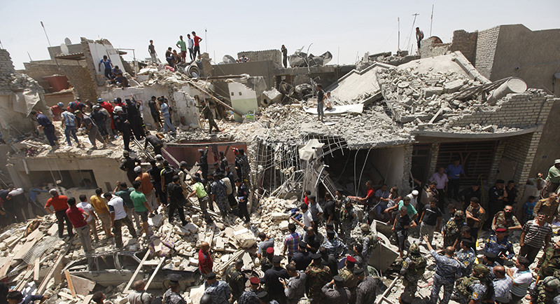 People stand outside damaged houses after an Iraqi plane accidentally dropped a bomb in Ni'iriya district in Baghdad July 6, 2015 (Reuters Photo)