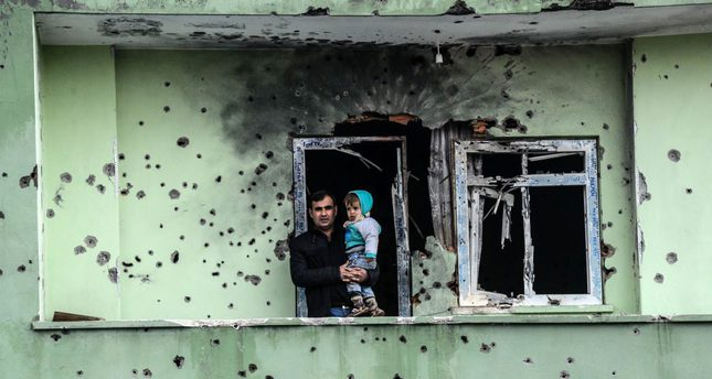 A man holds an infant on the balcony of a damaged house that was used by PKK terrorists in the Silopi district of Şırnak province.