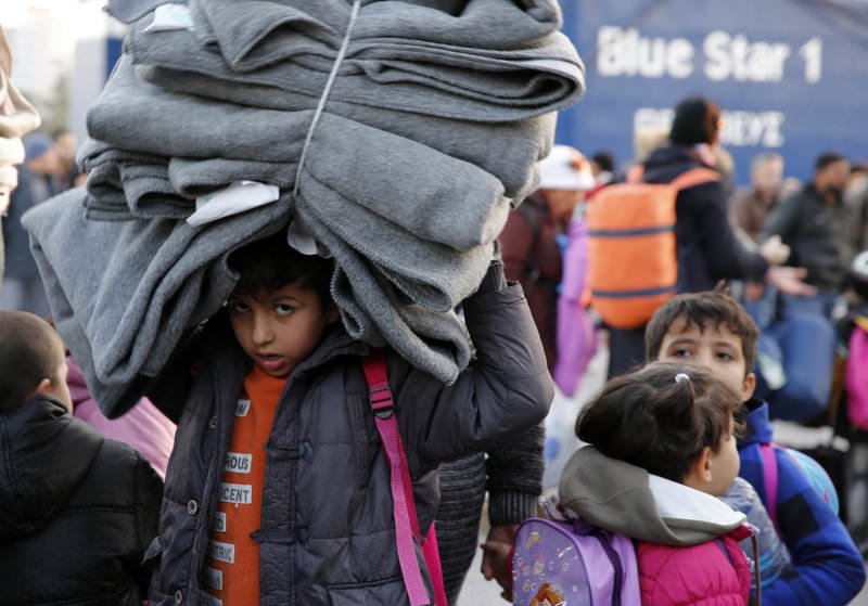 A migrant child carries blankets as refugees and migrants disembark from the passenger ferry Blue Star1 at the port of Piraeus, near Athens, Greece, on Jan. 31.