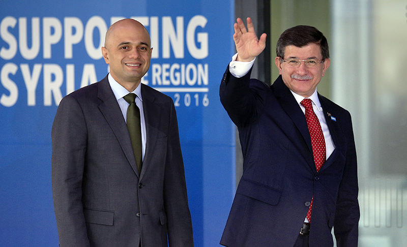 British MP Sajid Javid, left, welcomes as Turkish Prime MinisterAhmet Davutou011flu waves as he arrives at the Queen Elizabeth II Conference Centre in London where world leaders are meeting for talks over the Syrian refugee crisis (AP Photo)