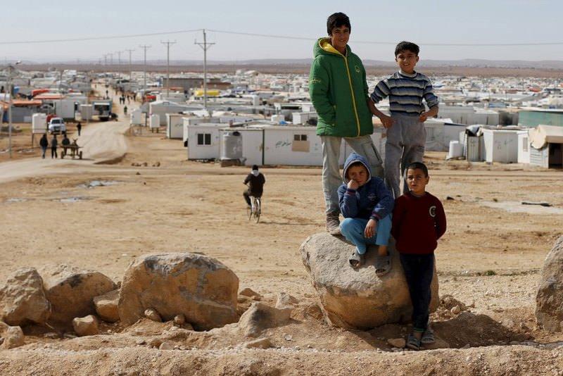 Syrian refugee children standing on a rock in Al Zaatari refugee camp in the Jordanian city of Mafraq.