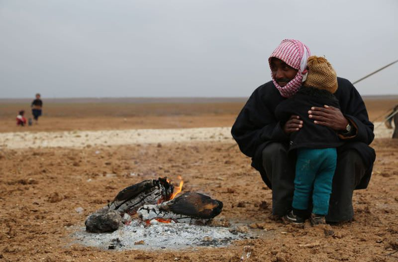 An Iraqi refugee and his child who fled the northern city of Mosul, now held by DAESH, pictured in a new camp on the outskirts of Syrian town Ras al-Ain, near the border with Turkey.