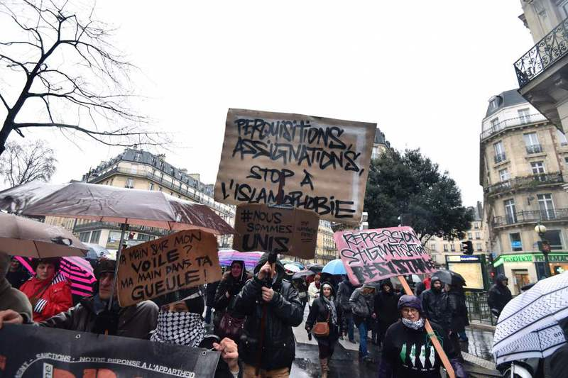 People holding placards reading ,Searches, summons, stop to the Islamophobia, take part in a demonstration on Jan. 30 in Paris.