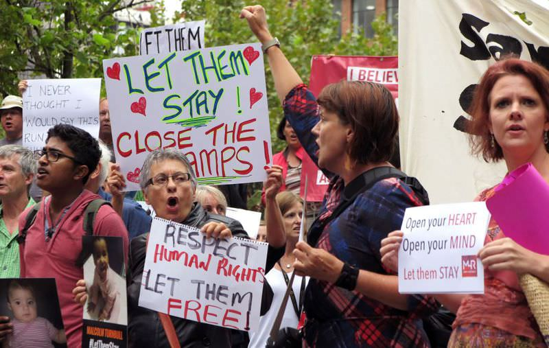 People hold up placards at a protest outside an immigration office in Sydney on Feb. 4. (AFP Photo)