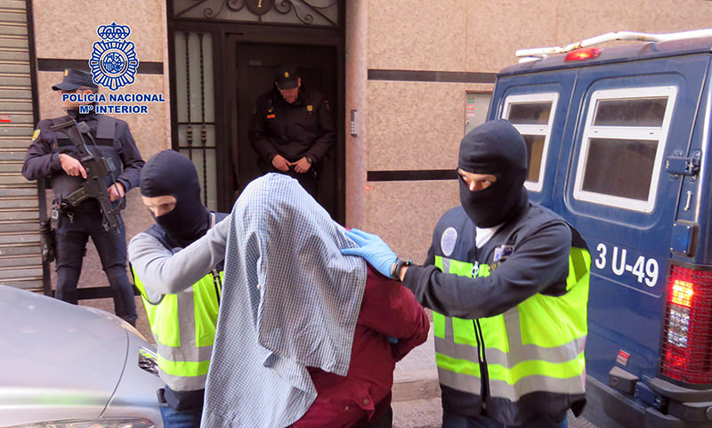 A handout picture released on February 7, 2016 by Spanish National Police shows masked police officers taking an arrested person at an undisclosed location. (AFP Photo)