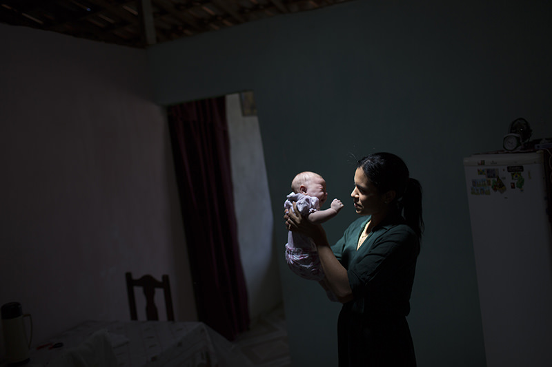 Juliana da Silva, is illuminated by a ray of sunlight as she poses for a photo holding her daughter Maria, who was born with microcephaly due to the Zika virus. (AP Photo)