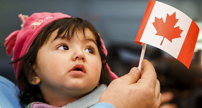 A young Syrian refugee looks up as her father holds her and a Canadian flag at the as they arrive at Pearson Toronto International Airport in Mississauga, Ontario (Reuters Photo)