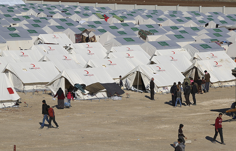 Displaced Syrians walk among a temporary refugee camp in northern Syria, near Bab al-Salameh border crossing with Turkey, Feb. 8, 2016. (AP)