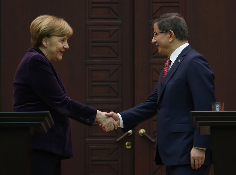 Turkish PM Davutou011flu (R) shook hands with German Chancellor Merkel after joint press conference.