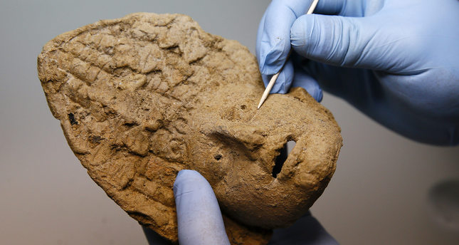 A baked clay mask that was discovered among the burial gifts provides information about the people whose bodies were buried in the chamber.
