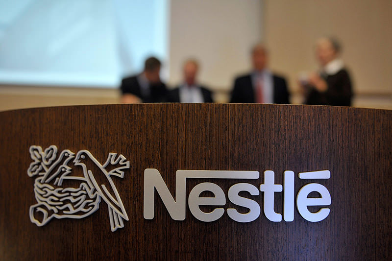 A file picture dated 19 February 2010 shows people behind a Nestle logo during a press conference of the food and drinks company Nestle in Vevey, Switzerland. (EPA Photo)
