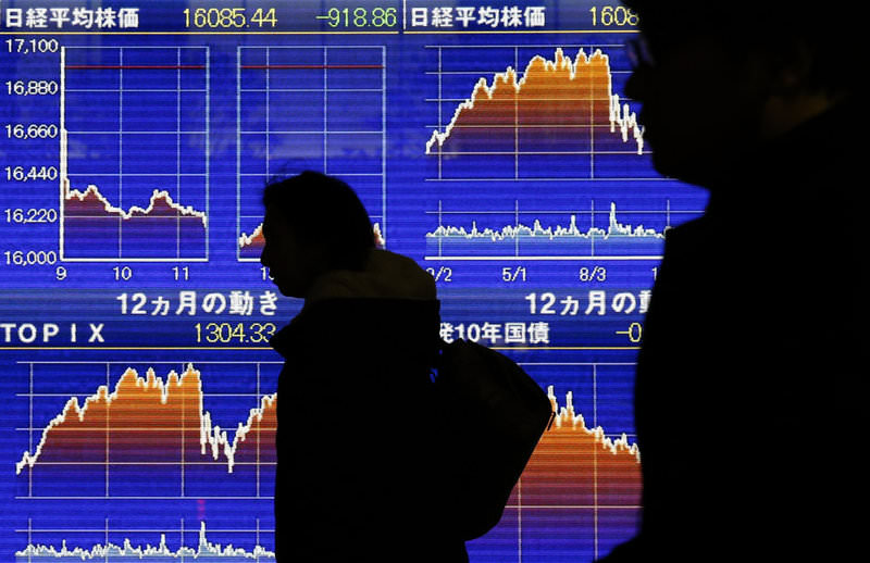 Pedestrians walk past an electronic board showing the graphs of the recent fluctuations of Japan's Nikkei average outside a brokerage firm in Tokyo, Japan, on Feb. 9.