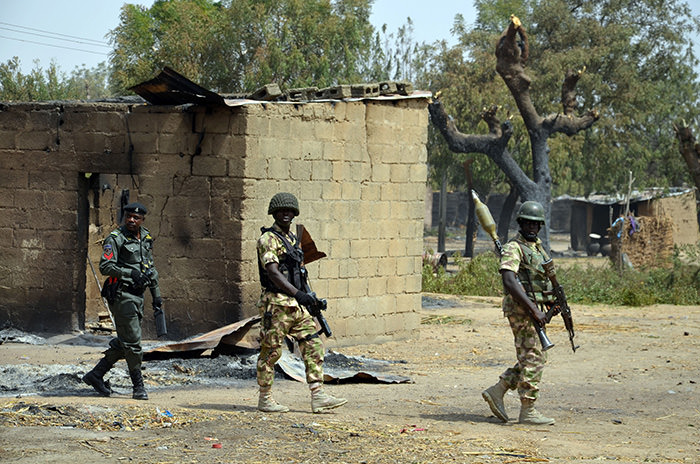 Security forces walk past burnt house on February 4, 2016 during a visit to the village of Dalori village,in northeastern Nigeria (AFP Photo)