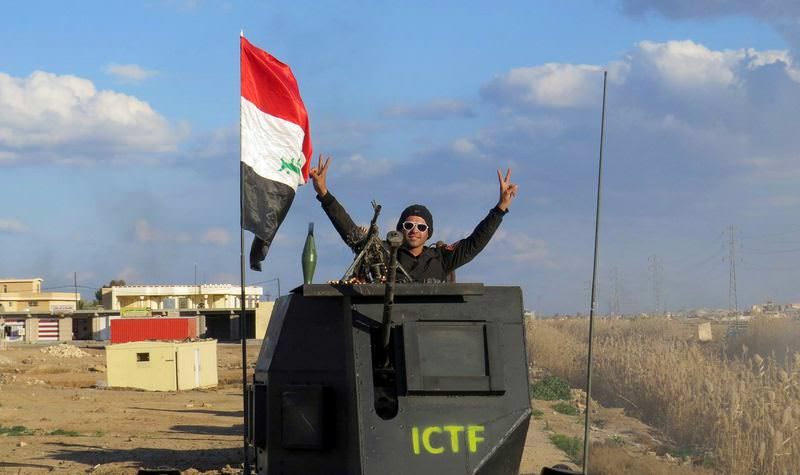 A member of teh Iraqi security forces celebrate the victory after DAESH militants were driven out of Ramadi's outskirts.