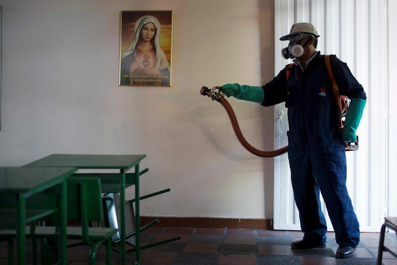 A city worker sprays insecticide to kill mosquitoes after class hours at a school in Cucuta, capital of Norte de Santander state, on Colombia's northeastern border with Venezuela.