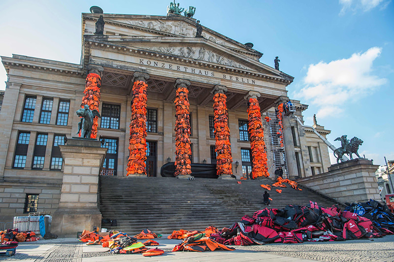 Assistants of Chinese artist Ai Weiwei decorate the columns of Berlin's Konzerthaus concert hall with lifejackets, on February 13, 2016. (AFP Photo)