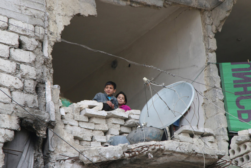Children looking from a partially destroyed home in Aleppo, Syria
