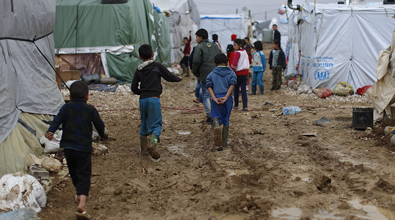 In this Monday, Jan. 4, 2016, file photo, Syrian refugee children walk in mud from the heavy rain at a refugee camp in the town of Hosh Hareem (AP Photo)