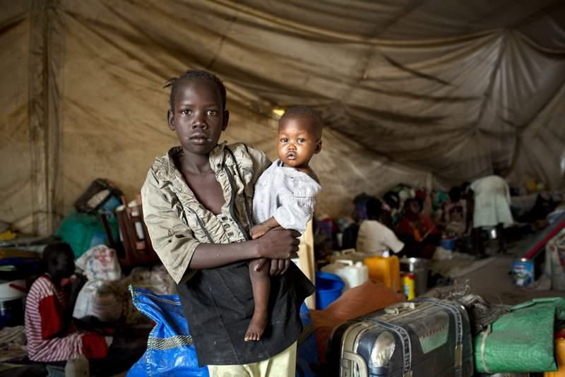 A handout photograph provided by the United Nations Children's Fund (UNICEF) on 30 March 2014 shows a young girl, displaced by recent fighting, holding her baby brother in a tent on the UN base (EPA Photo)