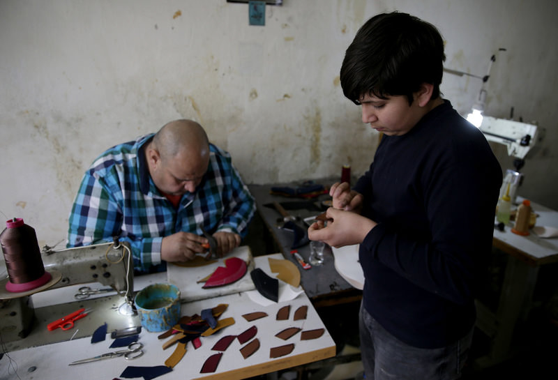 Khalid Bilal, a Syrian shoemaker, in his workshop in the western city of u0130zmir with his son. He is among the few Syrians with a steady income as he earns as much as TL 100 a day and complains of being forced to work illegally.