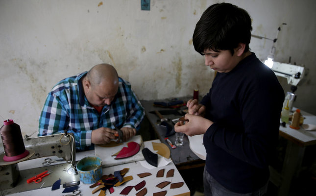 Khalid Bilal, a Syrian shoemaker, in his workshop in the western city of İzmir with his son. He is among the few Syrians with a steady income as he earns as much as TL 100 a day and complains of being forced to work illegally.