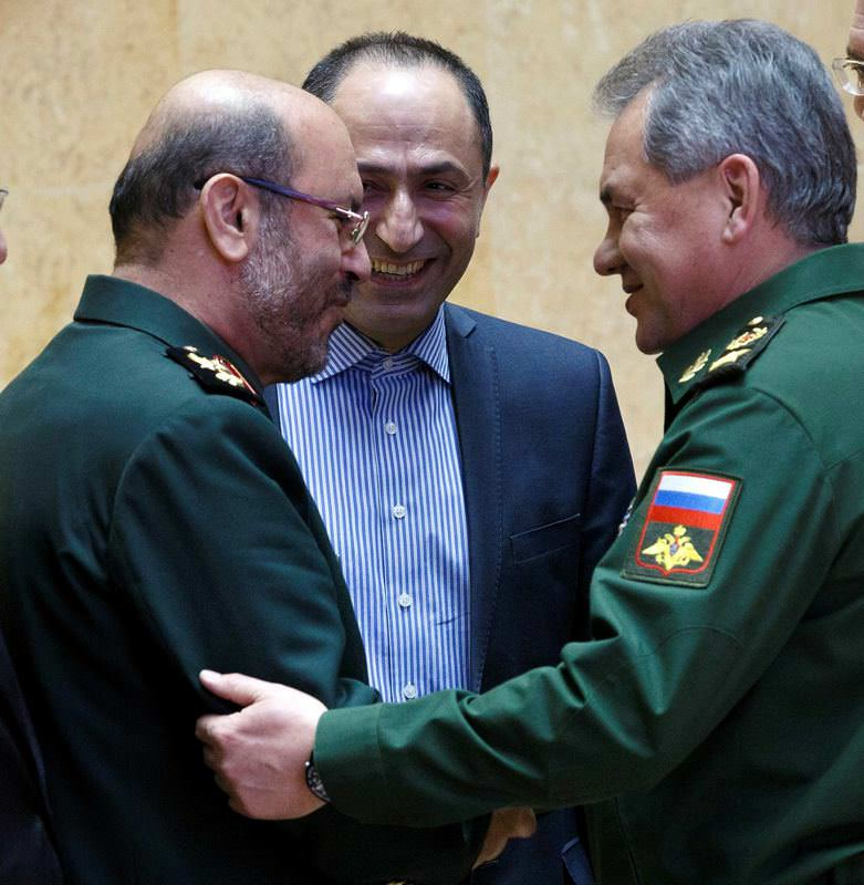 Russian Defense Minister Sergei Shoigu, right, and Iranian Defense Minister Hossein Dehghan shake hands during their meeting in Moscow.