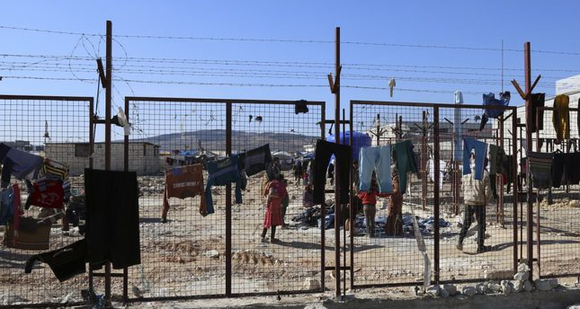 People walking around a temporary refugee camp built by the Turkish aid group IHH for displaced Syrians in northern Syria.