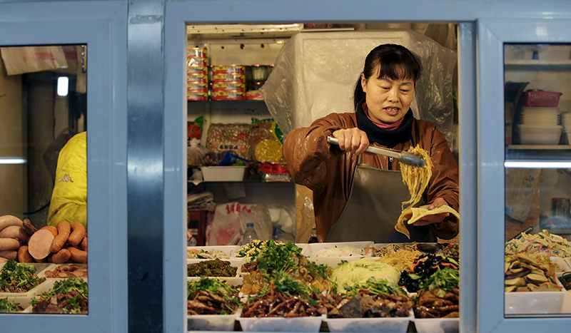 A vendor picks up food at her shop in a market in Beijing, February 18, 2016 (Reuters Photo)