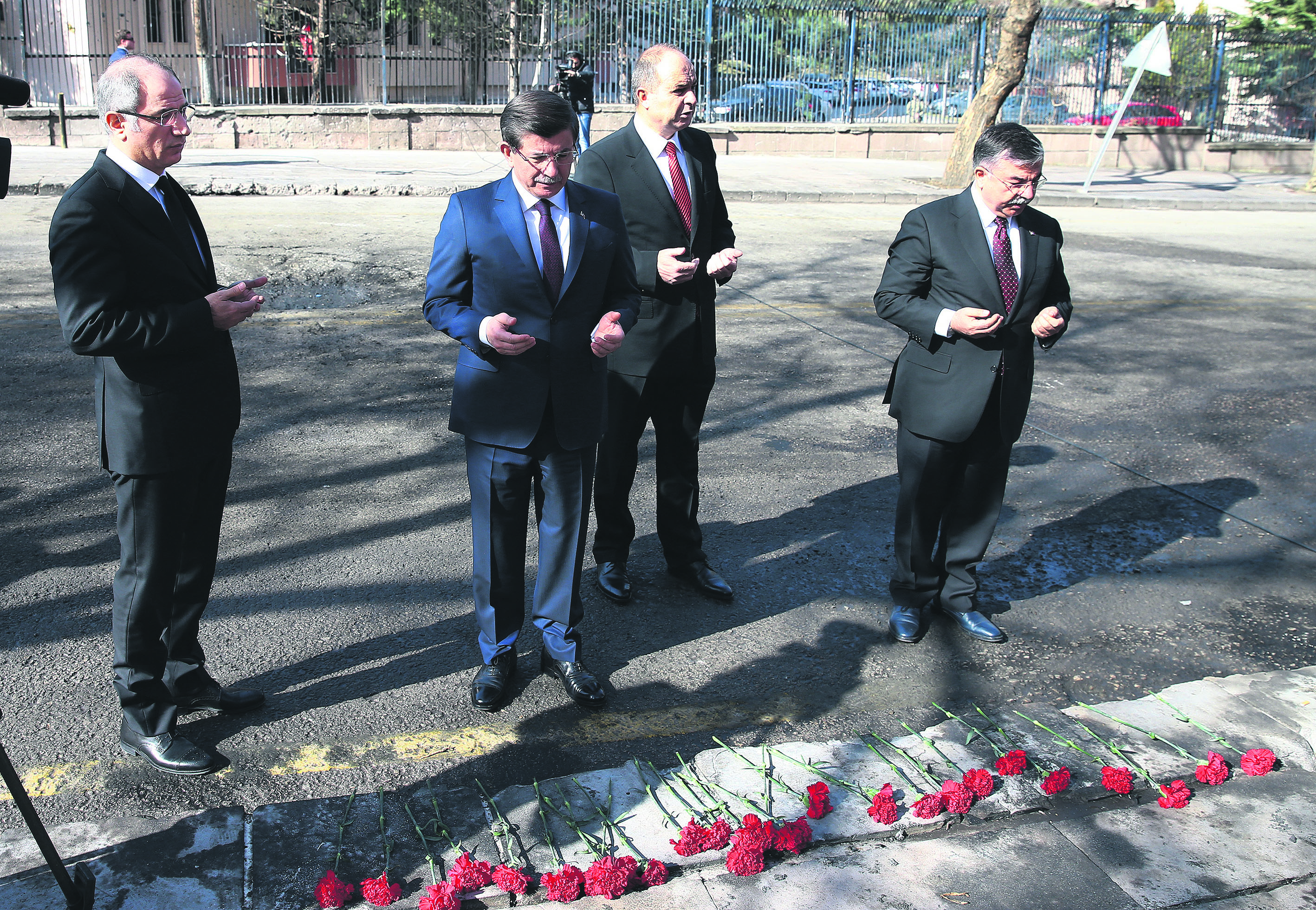 Prime Minister Ahmet Davutoğlu (C-L) and Cabinet ministers at the site of the blast on Friday where they paid tribute to the victims and laid carnations. (AA Photo)