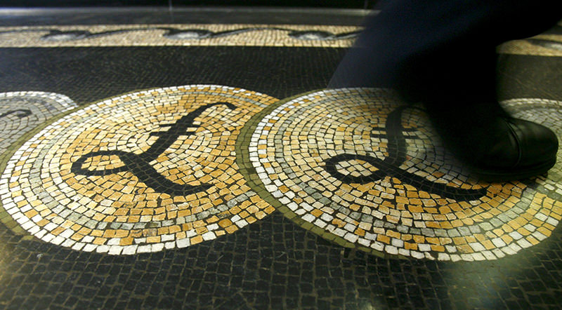 An employee is seen walking over a mosaic of pound sterling symbols set in the floor of the front hall of the Bank of England in London, on March 25, 2008. (REUTERS Photo)