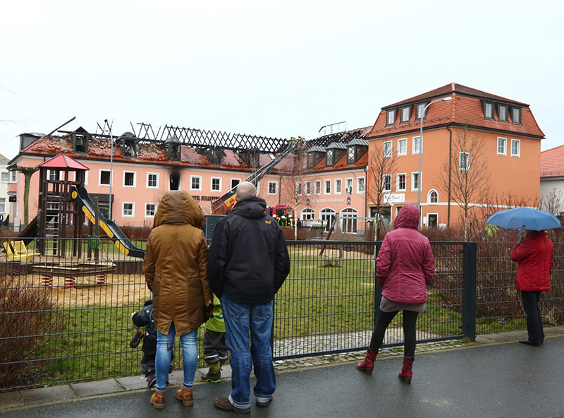 People look at burnt-out roof truss of a former hotel that was under reconstruction to become home for asylum seekers on Feb 21, 2016 in Bautzen, eastern Germany (AFP)