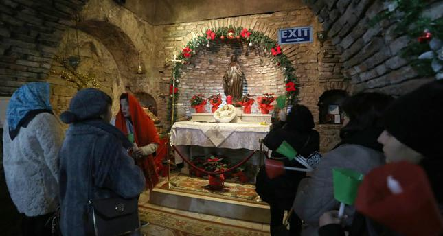 People praying at a Christmas service inside the House of the Virgin Mary in Selçuk. The site is popular among the Christian faithful.