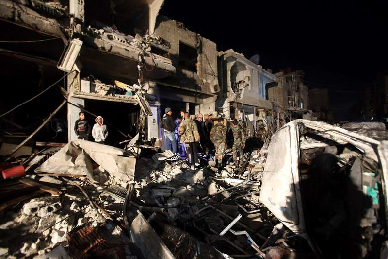 Syrians inspect a damaged building in Damascus after DAESH carried out suicide attacks that  left dozens dead.