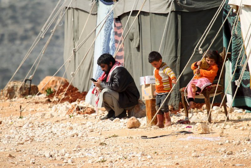 An internally displaced Syrian family that fled from Russian agression in Aleppo rests near tents in the village of Batabo in northern Idlib on Feb. 14.