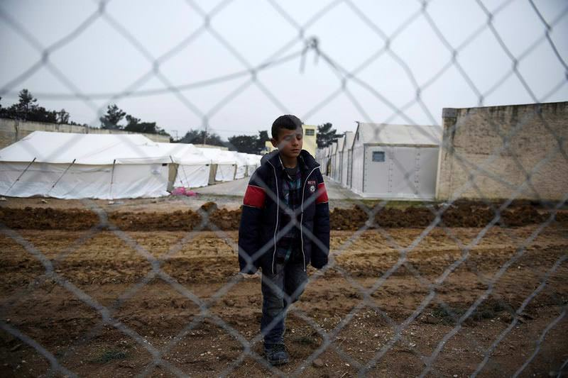 A boy stands behind a fence after the arrival of refugees and migrants at a transit center in the village of Diavata, west of the northern Greek city of Thessaloniki.