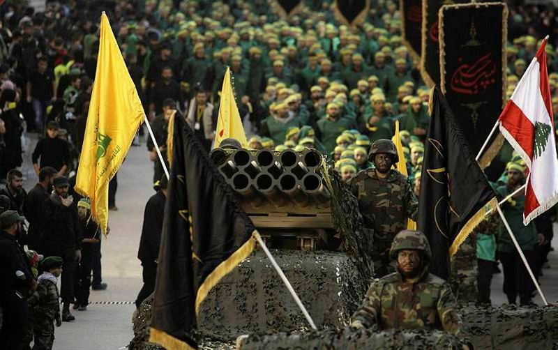 Members of Lebanon's militant Shiite group Hezbollah stand on a pick-up truck mounted with a multiple rocket launcher as they take part in a parade.
