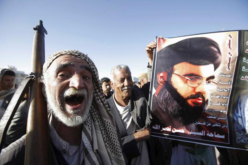 A Houthi militant shouts slogans as he stands next a poster of Lebanon's Hezbollah leader Hassan Nasrallah.