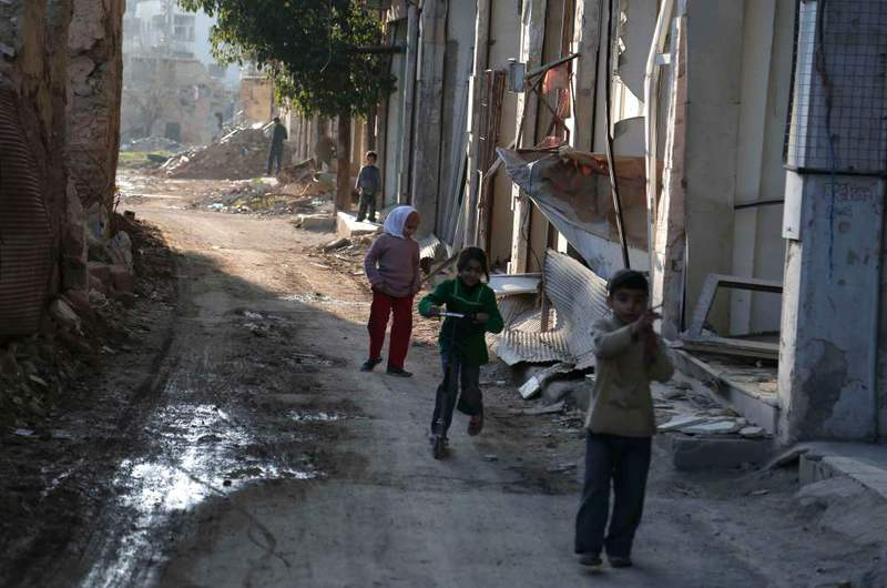 Syrian children playing between buildings destroyed by shelling in the Jobar neighborhood on the eastern outskirts of the capital Damascus, Syria.