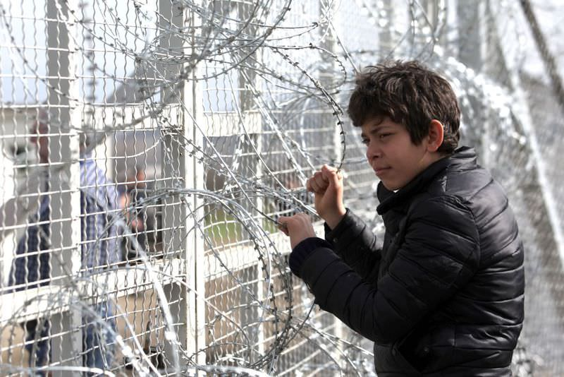 A boy yesterday looks through the barbed wire as migrants and refugees wait to cross the Greece-Macedonia border near the village of Idomeni.