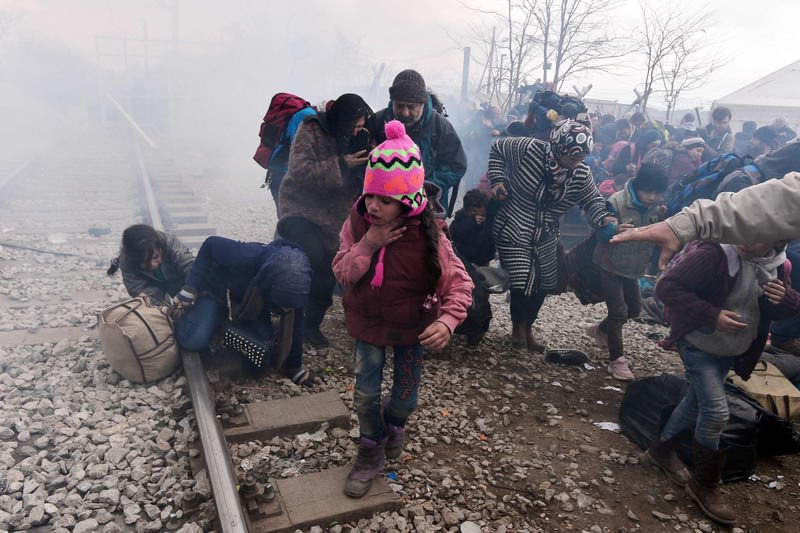 A child coughs as people run away after Macedonian police fired tear gas at hundreds of Iraqi and Syrian migrants who tried to break through the Greek border fence in Idomeni on Feb. 29.