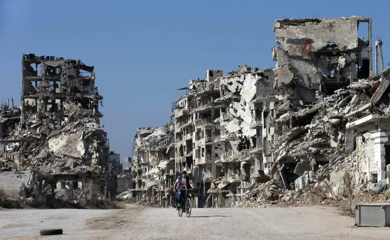 A Syrian boy rides a bicycle through a devastated part of the old city of Homs, Syria, Friday, Feb. 26.