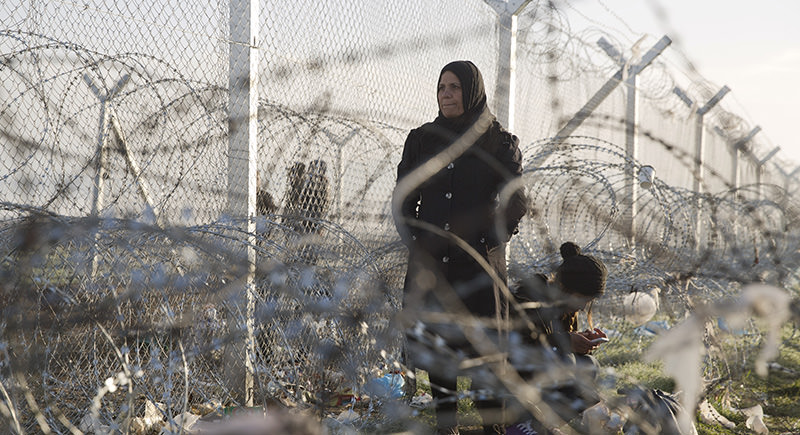 A woman stands while another crouches down to check her mobile phone near the border crossing in front to a wire fence that separates the Greek side from the Macedonian one at the northern Greek border station of Idomeni (AP Photo)