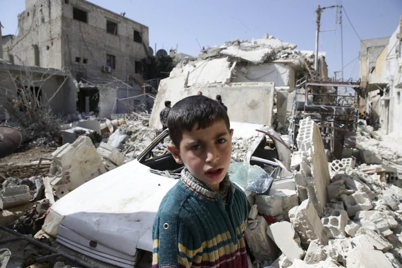 A boy looks on while residents inspect a damaged building in the opposition-held, besieged city of Douma.
