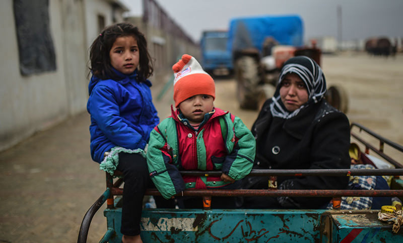Refugee children arrive a the Turkish border crossing gate as Syrians fleeing the northern embattled city of Aleppo wait on February 6, 2016 in Bab-Al Salam, near the city of Azaz, northern Syria (AFP Photo)